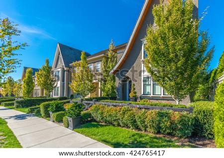 Nice and comfortable neighborhood. Townhouses on the empty street. - stock photo