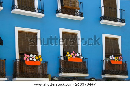 nice balconies with colorful flowers in a blue and white house - stock photo