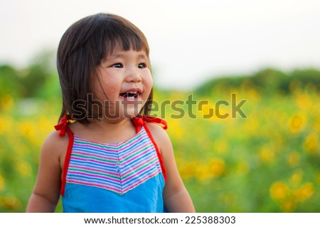 nice big smile from asian children on sunflower field - stock photo