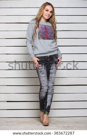Nice blond woman in gray hoody and black jeans posing near white wooden wall - stock photo