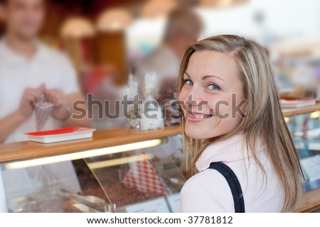 nice blonde female smiling while buying some roasted nuts at the octoberfest - stock photo
