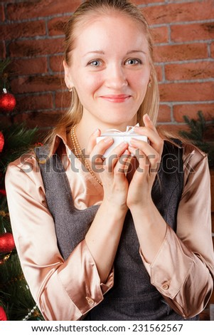 Nice blonde woman holding white gift box under the Christmas tree - stock photo