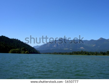 Nice blue sky above a mountain covered landscape - stock photo