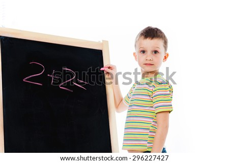 Nice boy trying answer simple math question; preschooler child writing basic math equation on a chalkboard; preschooler kid staying nearby chalkboard with a peace of chalk - stock photo