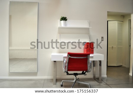 Nice bright contemporary modern desk with red office chair, red binders and rectangular mirror. - stock photo