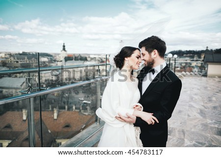 Nice brunette bride and bridegroom standing close to each other at old city background and smiling, wedding photo. - stock photo