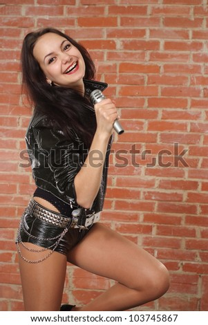 Nice Caucasian female with a microphone singing against a brick wall - stock photo