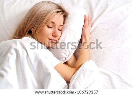 Nice Caucasian woman sleeping on the bed - stock photo