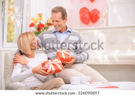 Nice celebration. Pleasant vivacious smiling adult couple holding presents and sitting in the armchair while celebrating St Valentine day - stock photo