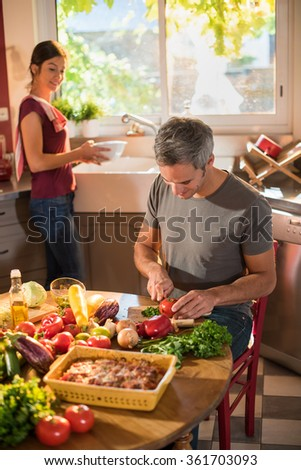 Nice couple cooking together a vegetable meal in the kitchen by a sunny day. The grey haired man is cutting a tomato and the woman is doing the dishes. They are wearing casual clothes. - stock photo