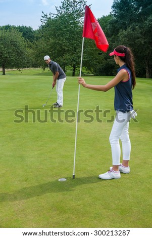 Nice couple playing golf on a green course during a sunny day. The woman is holding the red flag pole while her partner is swinging his club, aiming at the hole They are wearing sportswear outfits - stock photo