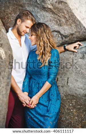 Nice couple standing together very close to each other between rocks, outdoor. Beloved holding hands of each other. Man looking down and she has closed eyes. Profile. - stock photo