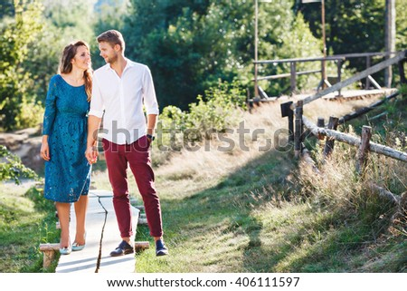 Nice couple walking together, outdoor, in the countryside. Woman wearing blue dress and light blue shoes and man wearing white shirt, claret trousers and black shoes. Full body - stock photo