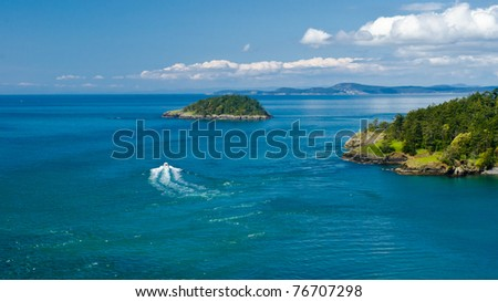 Nice cruise yacht in the Pacific Ocean over green shoreline and small island and blue sky with white clouds. - stock photo