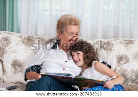 Nice elderly woman grandmother reading story to happy granddaughter. Happy family at home concept - stock photo