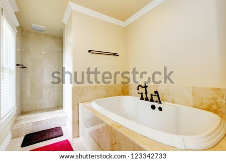 Nice empty bathroom with large white tub and walk-in shower. - stock photo