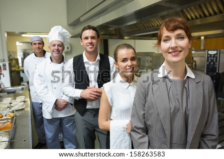 Nice female manager posing with the staff in a professional kitchen  - stock photo