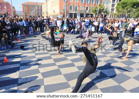 NICE, FRANCE â?? APRIL 11, 2015: A group of street dancers performing a break dance routine on Place Massena in Nice, France. - stock photo