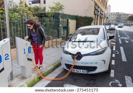 NICE, FRANCE â?? APRIL 11, 2015: A woman is programming the Auto Bleue charging station to electrically charge a Renault Zoe electric car in Nice, France. - stock photo
