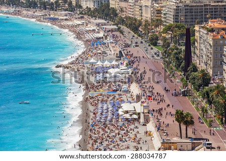 NICE, FRANCE - AUGUST 23, 2014: Beach and promenade of Nice - fifth most populous, second-largest on French Mediterranean coast and one of most visited cities with 4 million tourists every year. - stock photo