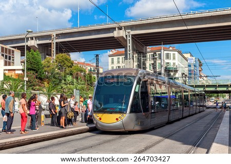 NICE, FRANCE - AUGUST 23, 2014: Modern tramway at tram stop. Nice tramway is single-line tramway opened on November 24, 2007 replacing old bus lines and providing a frequency of five minutes. - stock photo
