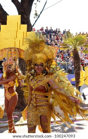 NICE, FRANCE - FEBRUARY 22: Carnival of Nice, Flowers' battle. This is the main winter event of the Riviera. Young smiling woman dressed in golden carnival costume. Nice, France - Feb 22, 2012 - stock photo