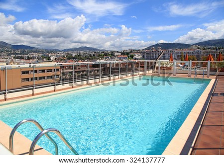 NICE, FRANCE - MAY 17, 2013: Swimming pool on the roof of resort with urban view, Nice, France - stock photo