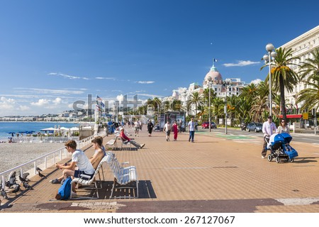 NICE, FRANCE - OCTOBER 2, 2014: People enjoying sunny weather and view of Mediterranean sea at English promenade (Promenade des Anglais), a great place for walking, jogging, biking or simply relaxing. - stock photo