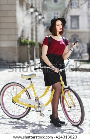Nice girl in burgundy shirt, black skirt and hat with bag on bicycle holding phone. Looking aside, full body. Cycling, outdoor, city - stock photo