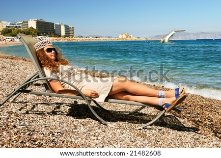 Nice girl lying on chaise on the beach at the sea resort - stock photo