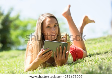 Nice girl lying on grass in meadow enjoying reading  ereader - stock photo
