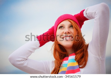 Nice girl wearing vibrant winter clothing looking up to the sky - stock photo