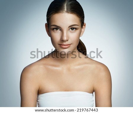 Nice girl with makeup / portrait of a gorgeous brunette smiling girl on blue background  - stock photo