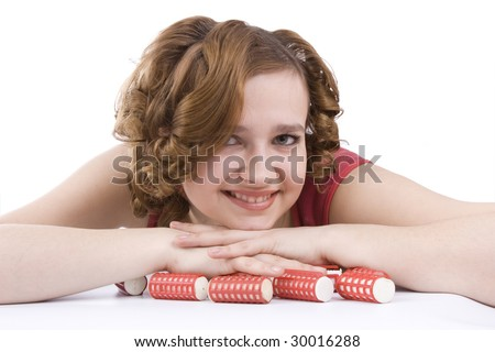 Nice girl with red hair-curlers. Smiley woman with hair-rollers. Young attractive housewife with curlers in hair. Isolated on white in studio. - stock photo