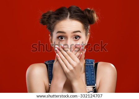 Nice girl, with top knot hairdo, wearing on denim jumpsuit, closing her mouth by her hands like she said something wrong, on the red background, in studio, waist up - stock photo