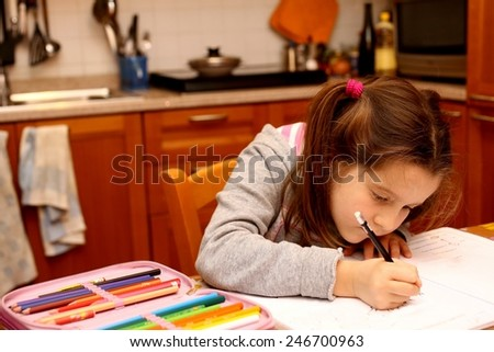 nice girl writes with pencil her homework in the kitchen - stock photo