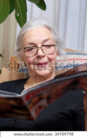 Nice grandmother read magazine - stock photo