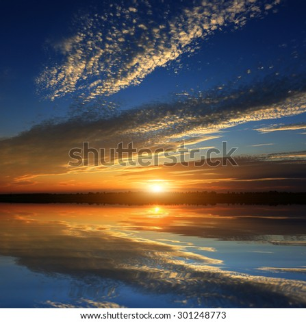 Nice hot sunset over lake water - stock photo