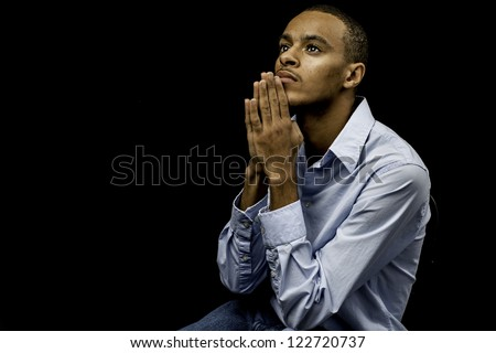 Nice isolation of a young african american black male praying with plenty of space for custom text - stock photo