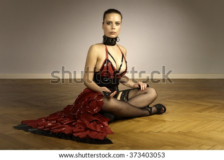Nice lady in sexy latex apparel sitting on floor - stock photo
