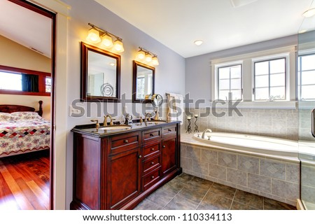 Nice lavender bathroom with tub and wood cabinet with two sinks and tile floor. - stock photo
