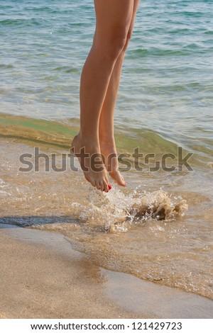 nice legs of a pretty girl walking in water - stock photo
