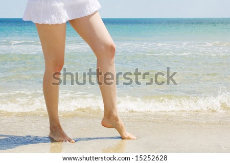 nice legs on the beach, beautiful blue sea background - stock photo