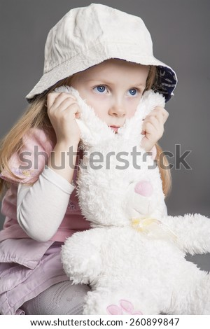 Nice Little Female Child Holding Toy and Dreaming, Isolated Against Gray Background. Vertical Image Composition - stock photo