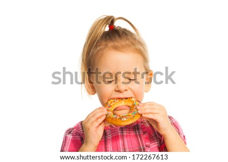 Nice little girl biting bread ring isolated on white with closed eyes - stock photo