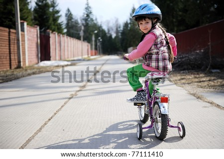 Nice little girl in blue helmet riding her bike - stock photo