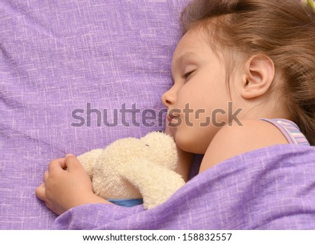 nice little girl sleeping in her bed at home - stock photo