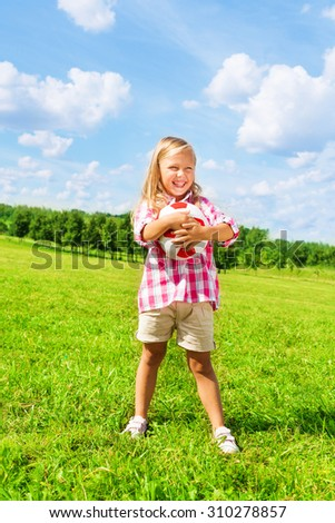 Nice little 6 years old blond cute girl in pink shirt holding soccer ball standing on the field on summer day - stock photo