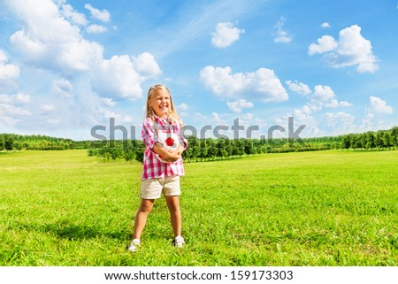 Nice little 6 years old blond cute girl in pink shirt with soccer ball standing in the park on sunny summer day - stock photo