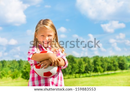 Nice little 6 years old blond cute smiling girl in pink shirt with soccer ball - stock photo
